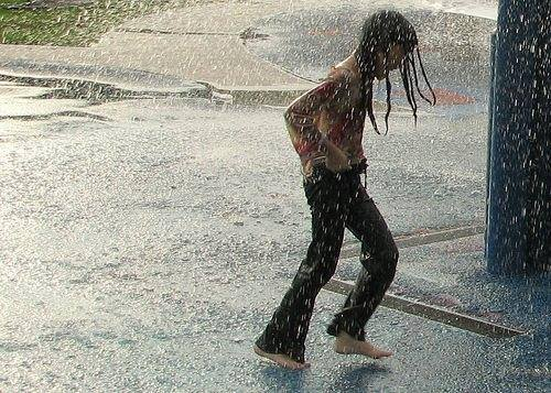 child dances in the rain in a Walmart parking lot