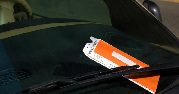violation ticket under the windshield wiper of a car