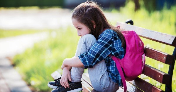 young girl sitting alone on a bench hugging her knees
