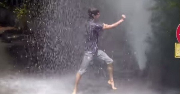 Man Dances In The Rain Of A Spraying Fire Hydrant