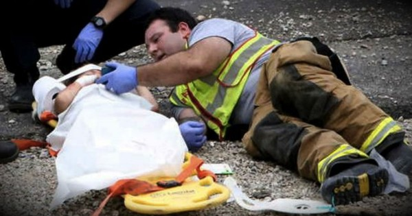 Firefighter Lays On Ground With Terrified Little Boy After Car Accident