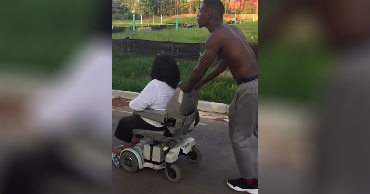 man pushes wheelchair