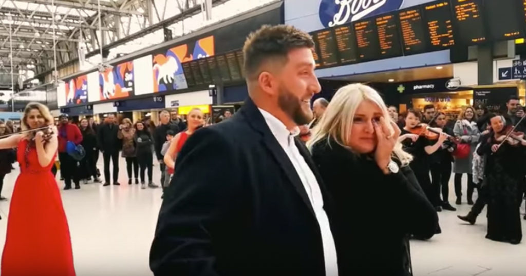 Surprise Orchestra Flash Mob Proposal At Busy Train Station