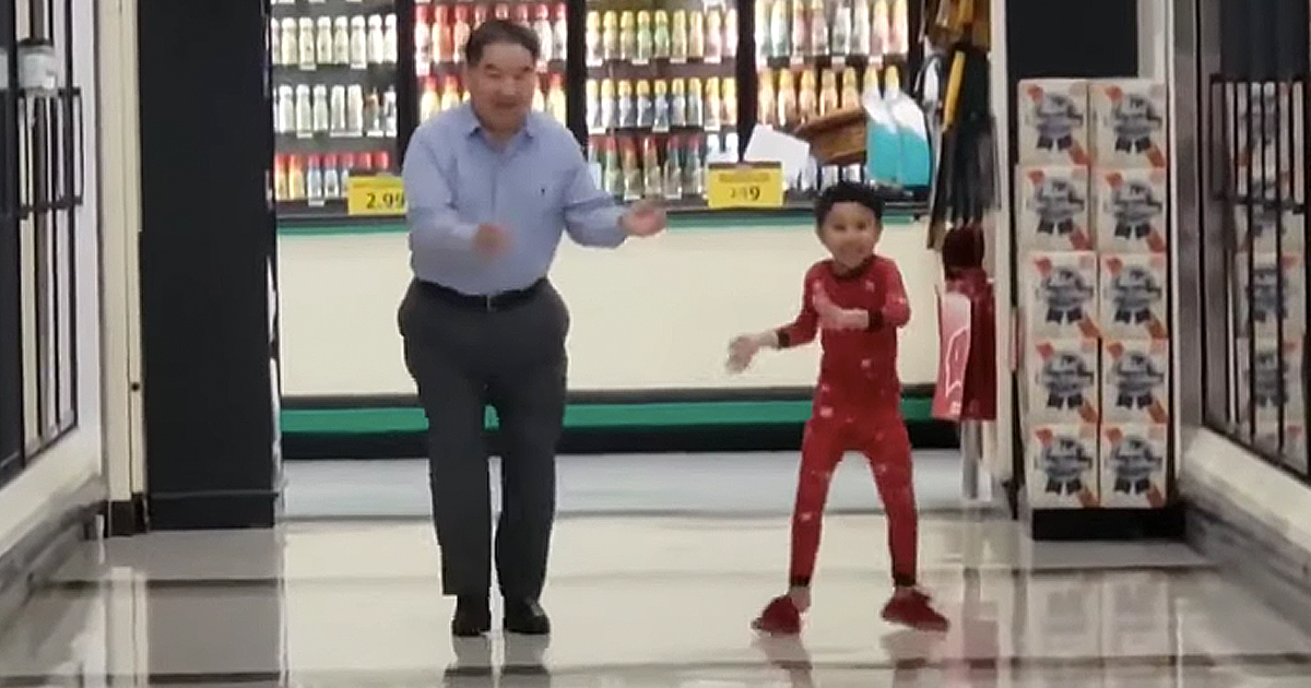 boy dances in supermarket