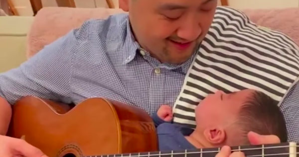 dad playing guitar for miracle baby