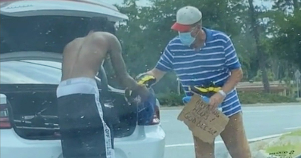 student gives clothes to homeless man